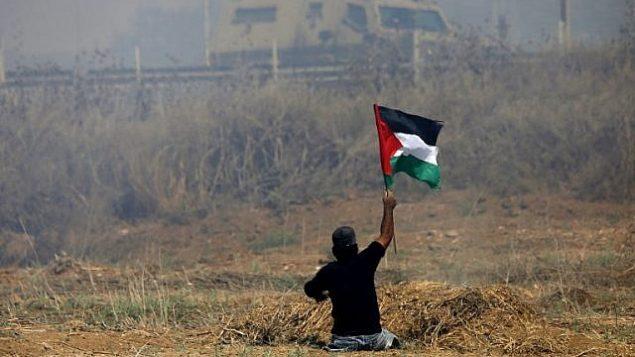 الشاب الفلسطيني إبراهيم أبو ثريا يلوح بالعلم الفلسطيني خلال مواجهات مع جنود إسرائيليين بالقرب من السياج الحدودي شرقي مدينة غزة، 19 مايو، 2017. (AFP PHOTO / MOHAMMED ABED/File)