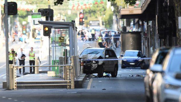 سيارة في منتصف الشارع بينما الشرطة وخدمات الاسعاف تعمل في اعقاب هجوم دهس في ملبورن، استراليا، 21 ديسمبر 2017 (MAL FAIRCLOUGH / AFP)