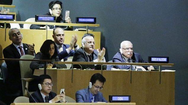 رياض منصور، السفير الفلسطيني لدى الأمم المتحدة، وأعضاء وفده يحتفلون بنتائج التصويت حول القدس في قاعة الجمعية العامة، 21 ديسمبر، 2017، في مقر الأمم المتحدة في نيويورك. (AFP PHOTO / EDUARDO MUNOZ ALVAREZ)