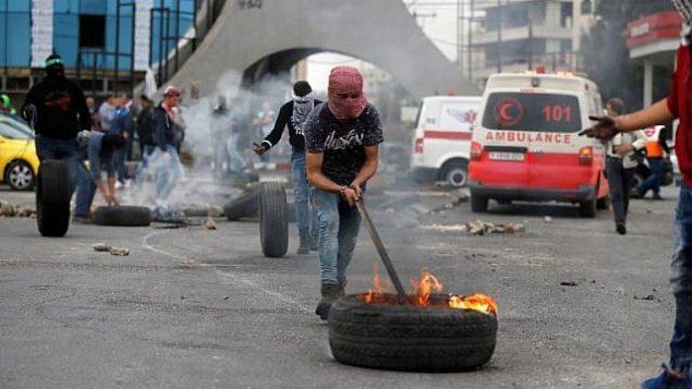 محتجون فلسطينيون يحرقون الإطارات أثناء اشتباكات مع حرس الحدود الإسرائيليين شمال رام الله في الضفة الغربية في 22 ديسمبر / كانون الأول 2017. (Abbas Momani/AFP)