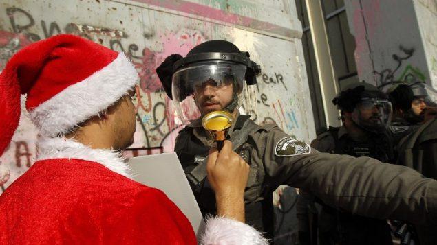 متظاهر فلسطيني يرتدي بدلة سانتا كلوز يواجه شرطي حرس حدود إسرائيل خلال تظاهرة عند المدخل الرئيسي لمدينة بيت لحم، 23 ديسمبر، 2017. (AFP PHOTO / Musa AL SHAER)