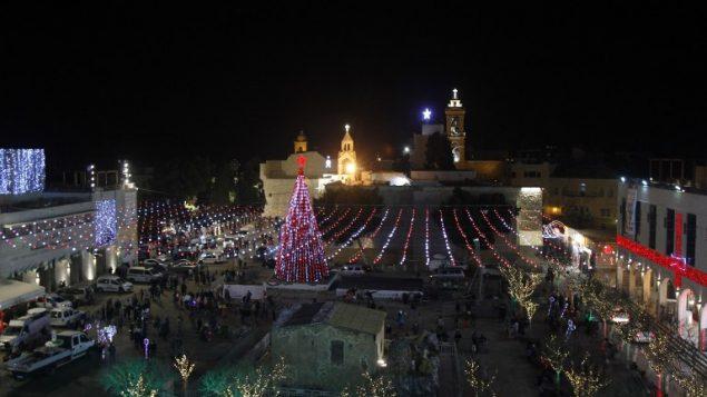 صورة تم التقاطها في 23 ديسمبر، 2017 لزينة عيد الميلاد في ساحة المهد وكنيسة المهد (في الخلفية) في مدينة بيت لحم  في الضفة الغربية. (AFP PHOTO / Musa EL SHAER)