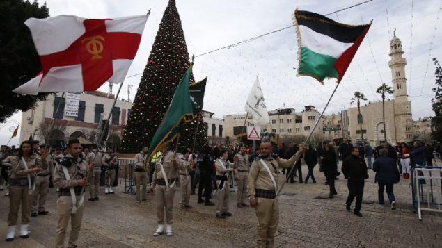 الكشافة المسيحيةي الفلسطينية تقدم عرضا في ساحة المهد  خارج كنيسة المهد مع احتشاد المحتفلين بعيد الميلاد في مدينة بييت لحم في الضفة الغربية، 24 ديسمبر، 2017. ( AFP PHOTO / HAZEM BADER)