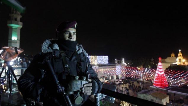 شرطي فلسطيني يقوم بحراسة ساحة المهد خارج كنيسة المهد مع احتشاد المحتفلين بليلة عيد الميلاد في مدينة بييت لحم في الضفة الغربية، 24 ديسمبر، 2017. (AFP PHOTO / Musa AL SHAER)
