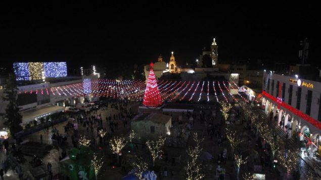 أشخاص يشاركون في احتفالات ليلة عيد الميلاد في ساحة المهد خارج كنيسة المهد في مدينة بييت لحم في الضفة الغربية، 24 ديسمبر، 2017. (AFP PHOTO / Musa AL SHAER)