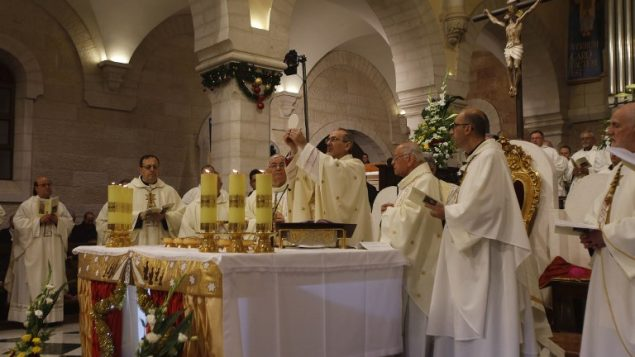 المدبر الرسولي لبطريركية اللاتين في القدس بيير باتيستا بيتسابالا يترأس قداس منتصف الليل بمناسبة عيد الميلاد في كنيسة المهد في مدينة بيت لحم في الضفة الغربية، 25 ديسمبر، 2017. (AFP PHOTO / POOL / MUSSA QAWASMA)