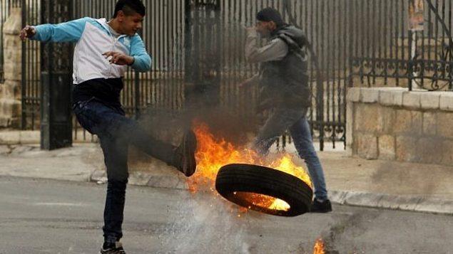 يشن متظاهر فلسطيني اطار مشتعل اثناء اشتباكات مع القوات الاسرائيلية في مدينة بيت لحم بالضفة الغربية في 29 كانون الاول 2017 بعد صلاة الجمعة. (AFP / Musa al Shaer)