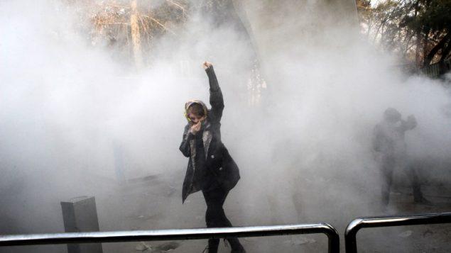 امرأة ايرانية ترفع قبضتها وسط الغاز المسيل للدموع في جامعة طهران خلال احتجاجات على الاوضاع الاقتصادية في البلاد، 30 ديسمبر 2017 (AFP PHOTO / STR)