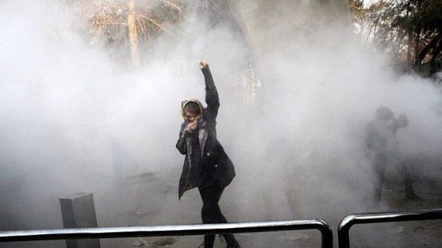 امرأة إيرانية ترفع قبضتها وسط دخان الغاز المسيل للدموع في جامعة طهران خلال احتجاج بسبب الغضب على المشاكل الاقتصادية، في العاصمة طهران في 30 ديسمبر 2017. (AFP PHOTO / STR)