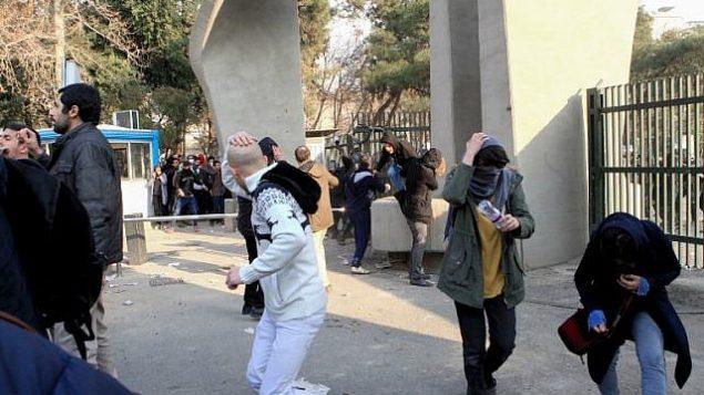 طلاب إيرانيون يحتمون من الغاز المسيل للدموع في جامعة طهران خلال مظاهرة بدافع الغضب على المشاكل الاقتصادية في العاصمة طهران في 30 ديسمبر 2017. (STR/AFP)