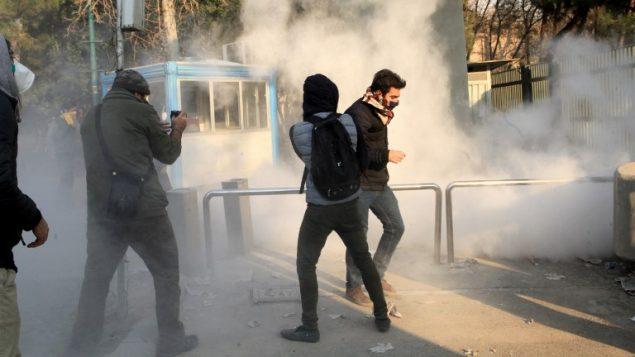 طلاب ايرانيون يفرون من الغاز المسيل للدموع في جامعة طهران خلال احتجاجات على الاوضاع الاقتصادية في البلاد، 30 ديسمبر 2017 (AFP PHOTO / STR)