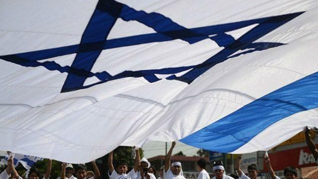 مجموعة مؤيدة لإسرائيل تلوح بعلم إسرائيلي عملاق خلال تظاهرة تضامن مع إسرائيل خلال حملة عسكرية في غزة في شوارع غواتيمالا سيتي في 3 أغسطس، 2014. ( AFP/ Johan ORDONEZ)