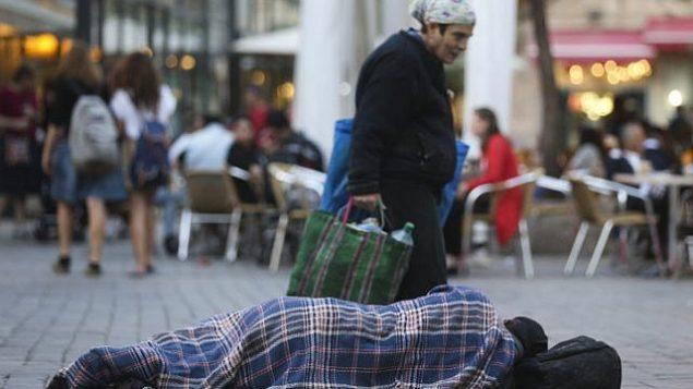 مارة يسيرون من أمام رجل مشرد ينام في الشارع، بالقرب من المقاهي في وسط مدينة القدس 10 نوفمبر، 2013. (Nati Shohat/FLASH90)