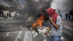شبان فلسطينيون يحملون حجارة خلال مواجهات مع الشرطة الإسرائيلية في حي صور باهر الواقع في القدس الشرقية، 7 أكتوبر، 2017. (Hadas Parush/Flash90)