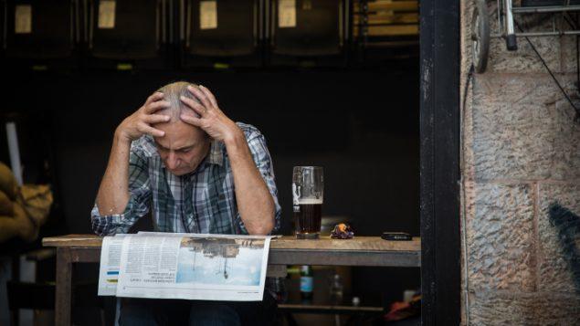 رجل يقرأ صحيفة في سوق محانيه يهودا في القدس، 5 سبتمبر 2017 (Hadas Parush/Flash90)
