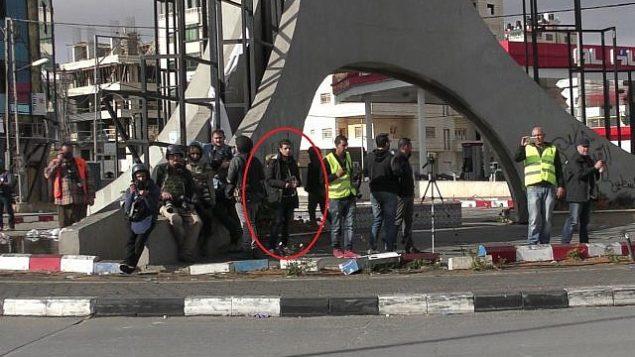 منفذ هجوم فلسطيني، يختبئ بين الصحافيين، قبل قيامه بطعن شرطي حرس حدود إسرائيلي في مدينة رام الله في الضفة الغربية، 15 ديسمبر، 2017. (الشرطة الإسرائيلية)