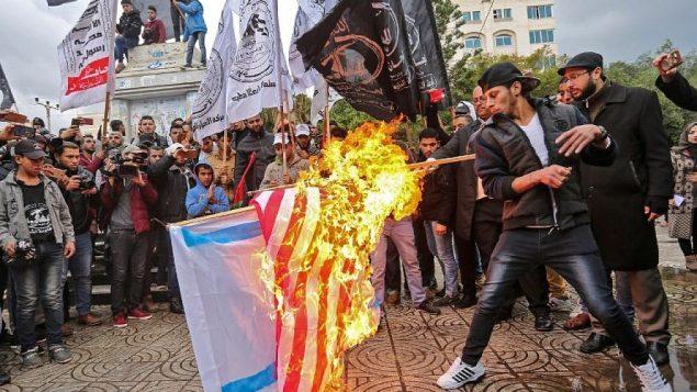فلسطينيون يحرقون الأعلام الأمريكية والإسرائيلية في مدينة غزة في 6 ديسمبر 2017 قبيل خطاب الرئيس الأمريكي دونالد ترامب AFP PHOTO / MAHMUD HAMS