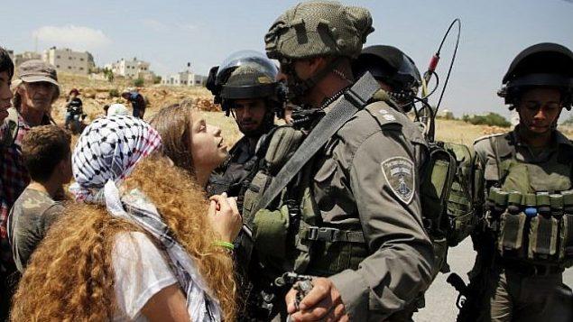 هذه الصورة من الأرشيف تم التقاطها في 12 مايو، 2017 لعهد التميمي (في وسط الصورة) خلال احتجاج أمام الجنود الإسرائيليين في قرية النبي صالح، شمال رام الله، في الضفة الغربية، بعد مظاهرة أجريت عقب صلاة الجمعة تضامنا مع الأسرى الفلسطينيين المضربين عن الطعام في السجون الإسرائيلية. (AFP/ ABBAS MOMANI)