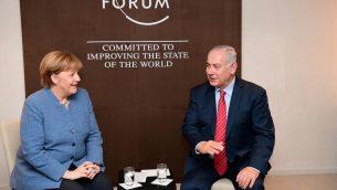 رئيس الوزراء بنيامين نتنياهو يلتقي بالمستشارة الالمانية انغيلا ميركل في المنتدى الاقتصادي العالمي في دافوس، سويسرا، 24 يناير 2018 (Amos Ben Gershon/ GPO)