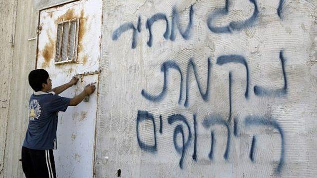 صورة توضيحية: صبي فلسطيني يفتح الباب بعد أن كتب على الجدران بالعبرية، ويزعم أن المستوطنون اليهود قاموا بذلك، في قرية عقربة في الضفة الغربية، بالقرب من مدينة نابلس، في 2 يوليو / تموز 2014. (AFP/JAAFAR ASHTIYEH)