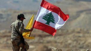 عنصر من منظمة حزب الله يحمل العلم اللبناني وعلم حزب الله خلال جولة لوسائل الإعلام بالقرب من بلدة عرسال الحدودية في 25 يوليو، 2017.   (AFP Photo/Stringer)