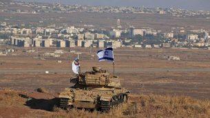 العلم الإسرائيلي يرفرف فوق حطام دبابة على تلة في هضبة الجولان تطل على الحدود مع سوريا في 18 أكتوبر، 2017. (AFP Photo/Jalaa Marey)