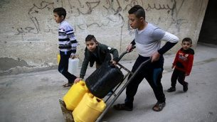 يحمل الأطفال الفلسطينيون المياه في مخيم الشاطئ للاجئين في مدينة غزة في 4 يناير / كانون الثاني 2018. (AFP PHOTO / MOHAMMED ABED)