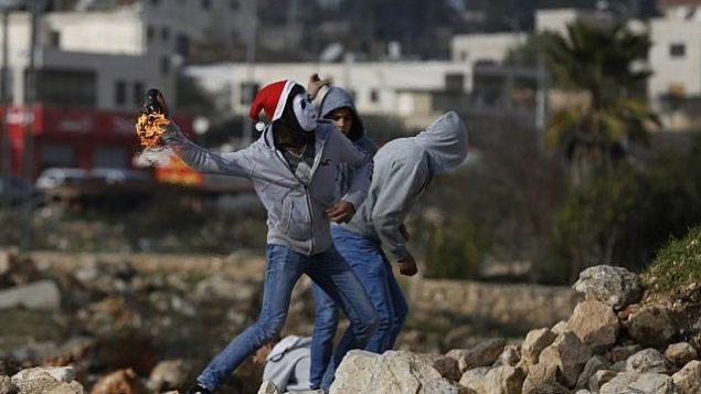 صورة للتوضيح: متظاهرون فلسطينيون يلقون بزجاجات حارقة باتجاه جنود إسرائيليين خلال مواجهات وقعت في 12 يناير، 2018 شمال مدينة رام الله في الضفة الغربية. (AFP PHOTO / ABBAS MOMANI)