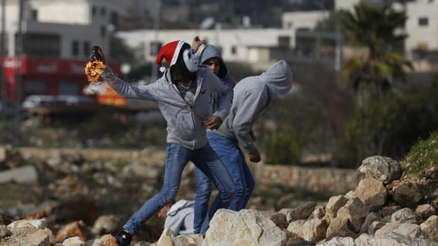 صورة توضيحية: متظاهرون فلسطينيون يلقون زجاجات حارقة باتجاه جنود اسرائيليين خلال اشتباكات في الضفة الغربية، 12 يناير 2018 (AFP PHOTO / ABBAS MOMANI)