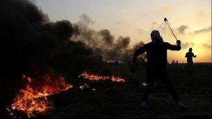 فلسطينيون في اشتباكات مع قوات الأمن الإسرائيلية في الضواحي الشرقية لمدينة غزة، بالقرب من الحدود مع إسرائيل، في 12 يناير / كانون الثاني 2018. (AFP Photo/Mohammed Abed)
