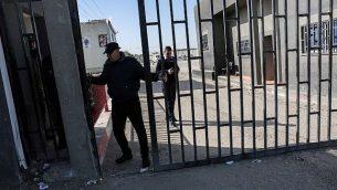 رجل امن فلسطيني يغلق بوابة معبر كرم ابو سالم بعد اغلاق الطرف الاسرائيلي من المعبر في اعقاب اكتشاف انفاق تمر تحتخ، في جنوب قطاع غزة، 14 يناير 2018 (AFP PHOTO / SAID KHATIB)