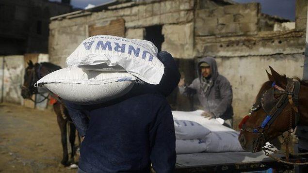 رجال فلسطينيون يحملون مساعدات غذائية امام مركز للأونروا في غزة، 15 يناير 2018 (AFP PHOTO / MOHAMMED ABED)