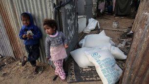 أطفال فلسطينيو يقفون بجانب أكياس مساعدات غذائية توفرها وكالة وكالة الأمم المتحدة لإغاثة وتشغيل اللاجئين الفلسطينيين في مخيم رفح للاجئين في جنوب قطاغ غزة، 24 يناير، 2017. (AFP Photo/Said Khatib)
