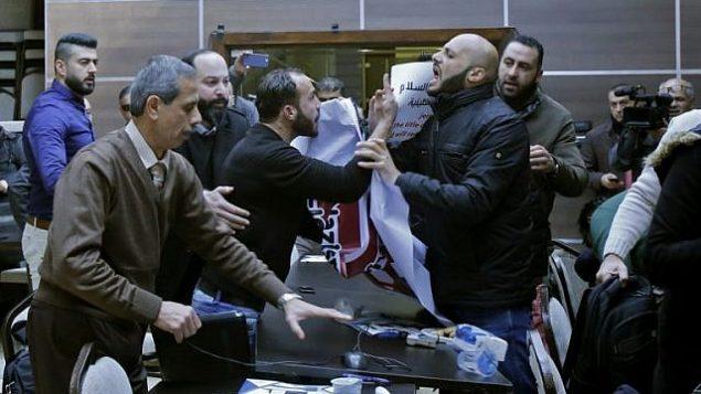نشطاء فلسطينيون يقاطعون دورة لقاء بين أعضاء في وفد اقتصادي أمريكي ورئيس الغرفة التجارية لمحافظة بيت لحم، في مدينة بيت لحم في الضفة الغربية، 30 يناير، 2018. (AFP Photo/Musa Al-Shaer)