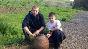 يوتام أريئيلي (من اليمين) وخاله عيدان أفيدور مع جرة بيزنطية تم اكتشافها في متنزه بيسان. (Shmuelik Armon)