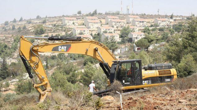 جرافة كاتربيلر تخلي ارض في الضفة الغربية لبناء منازل اسرائيلية، 2012 (Oren Nahshon/Flash90)