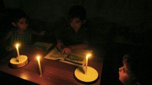 أطفال فلسطينيون يقومون بواجباتهم المنزلية على ضوء الشموع في منزل عائلتهم، خلال انقطاع الكهرباء في مخيم رفح للاجئين في جنوب قطاع غزة، في 18 سبتمبر / أيلول 2013. (Abed Rahim Khatib/Flash90)