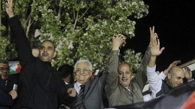 رئيس السلطة الفلسطينية محمود عباس، الثاني من اليسار،  يلوح للجماهير وبرفقته أسرى فلسطينيون محررون من السجون الإسرائيلية خلال احتفالات في مقر عباس في مدينة رام الله في الضفة الغربية. (Issam Rimawi/Flash90)