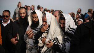 أصدقاء وعائلة الحاخام رازيئيل شيفاح، 35 عاما، في جنازته في حافات غلعاد في الضفة الغربية في 10 يناير 2018. (Miriam Alster/Flash90)