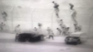 عشرات المهربين المصريين البدو على سلالم يقومون بإلقاء حزم ماريجوانا عبر الحدود إلى داخل إسرائيل، في محاولة تهريب كبيرة تحولت إلى معركة بالأسلحة النارية في 21 يناير، 2018. (Israel Police)