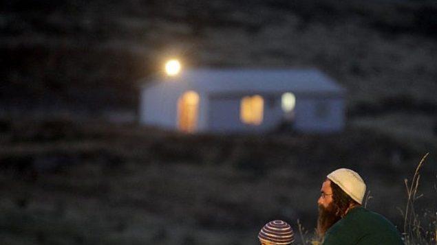 رجل وابنه بالقرب من بؤرة حفات غلعاد الاستيطانية. (Nati Shohat/ Flash 90)