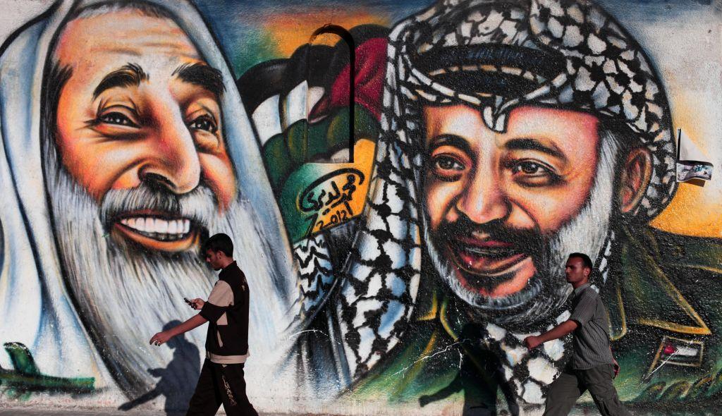فلسطينيون يمرون بجدار يصور الرئيس الفلسطيني الراحل ياسر عرفات في مدينة غزة يوم الأربعاء 4 يوليو / تموز 2012. (Wissam Nassar/Flash90)