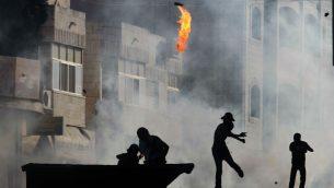 صورة توضيحية: متظاهر فلسطيني يلقي زجاجة حارقة خلال اشتباكات مع جنود اسرائيلية في قرية الرام بالقرب من رام الله، 27 سبتمبر 2013 (Issam Rimawi/Flash90)