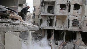 رجل سوري وسط الحطام بعد غارات جوية للنظام السوري في غوطة الشرقية، 22 فبراير 2018 (ABDULMONAM EASSA / AFP)
