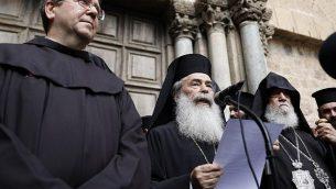 بطريرك الروم الأرثوذكس ثيوفيلوس الثالث يلقي ببيان للصحافة ويقف إلى جانبه حارس الأراضي المقدسة الأب فرانشيسكو باتون وكبير الأساقفة الأرمن سيفان (من اليسار)  من أمام أبواب الكنيسة في القدس، 25 فبراير 2018. (AFP/ GALI TIBBON)