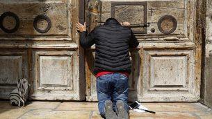 أحد الحجاج يصلي من أمام الأبواب المغلقة لكنيسة القيامة في البلدة القديمة في مدينة القدس، 25 فبراير، 2018. (AFP PHOTO / GALI TIBBON)