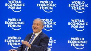 رئيس الوزراء بينيامين نتنياهو يضحك خلال مؤتمر في منتدى الاقتصاد العالمي السنوي في دافوس، 21 يناير، 2016. (AFP/FABRICE COFFRINI)