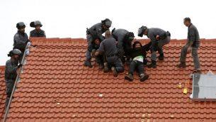 عناصر الشرطة الإسرائيلية تصل لإخلاء محتجين في 1 مارس، 2017 في مستوطنة عوفرا في الضفة الغربية، خلال عملية نفذتها القوات الإسرائيلية لهدم 9 مبان. (AFP Photo/Menahem Kahana)