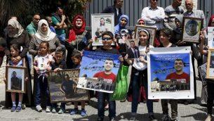 أسر أسرى فلسطينيين في السجون الإسرائيلية يتظاهرون أمام مكاتب الإتحاد الأوروبي في القدس الشرقية، 27 أبريل، 2017. (AFP/AHMAD GHARABLI)