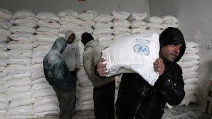 فلسطينيون يجمعون المساعدات الغذائية في مركز توزيع الأغذية التابع للأمم المتحدة في خان يونس جنوبي قطاع غزة، 28 يناير، 2018. (Said Khatib/AFP)